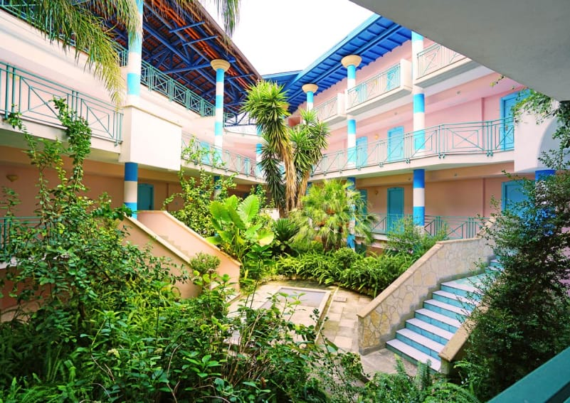 resort courtyard with blue pillars and pink walls image